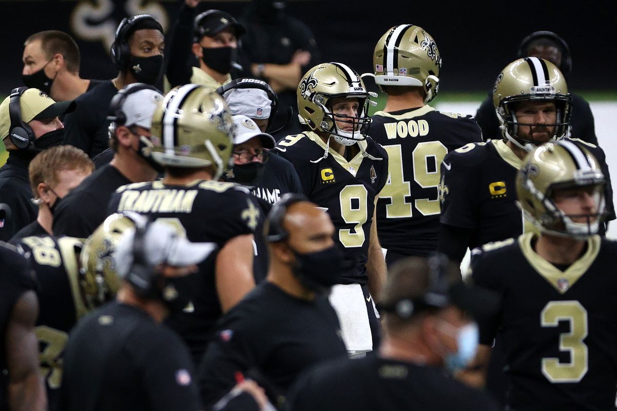 Drew Brees #9 of the New Orleans Saints stands on the sidelines among his teammates during their game against the San Francisco 49ers at Mercedes-Benz Superdome on November 15, 2020 in New Orleans, Louisiana.