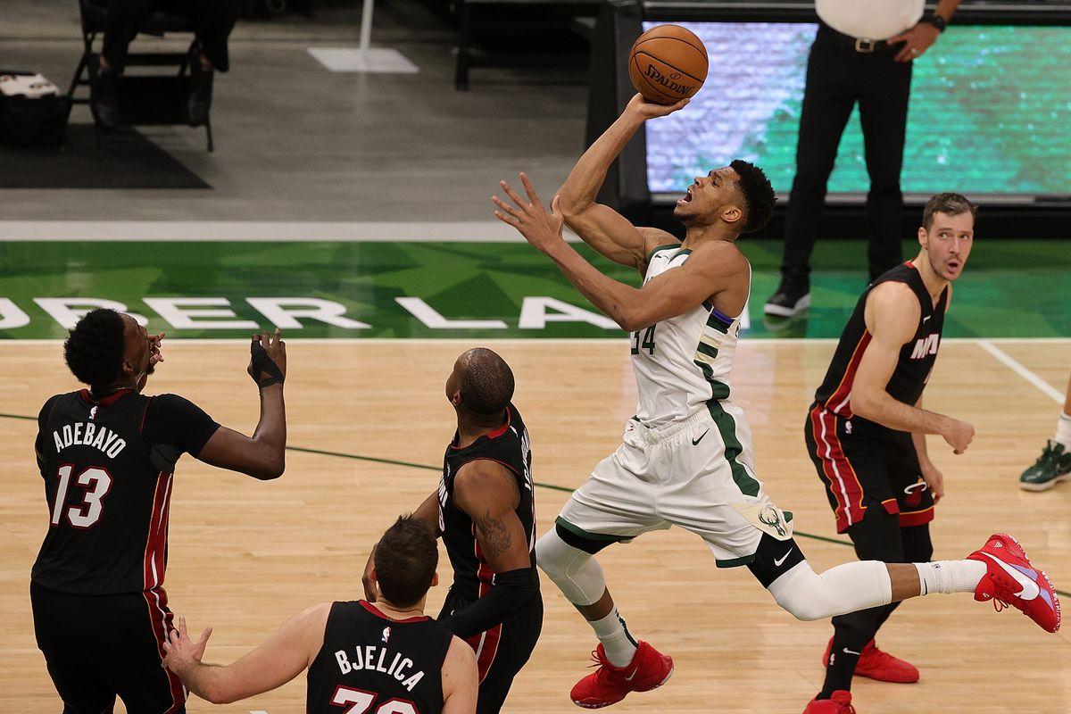 Giannis Antetokounmpo of the Milwaukee Bucks is fouled by Andre Iguodala of the Miami Heat during the second half of a game at Fiserv Forum on May 15, 2021 in Milwaukee, Wisconsin.