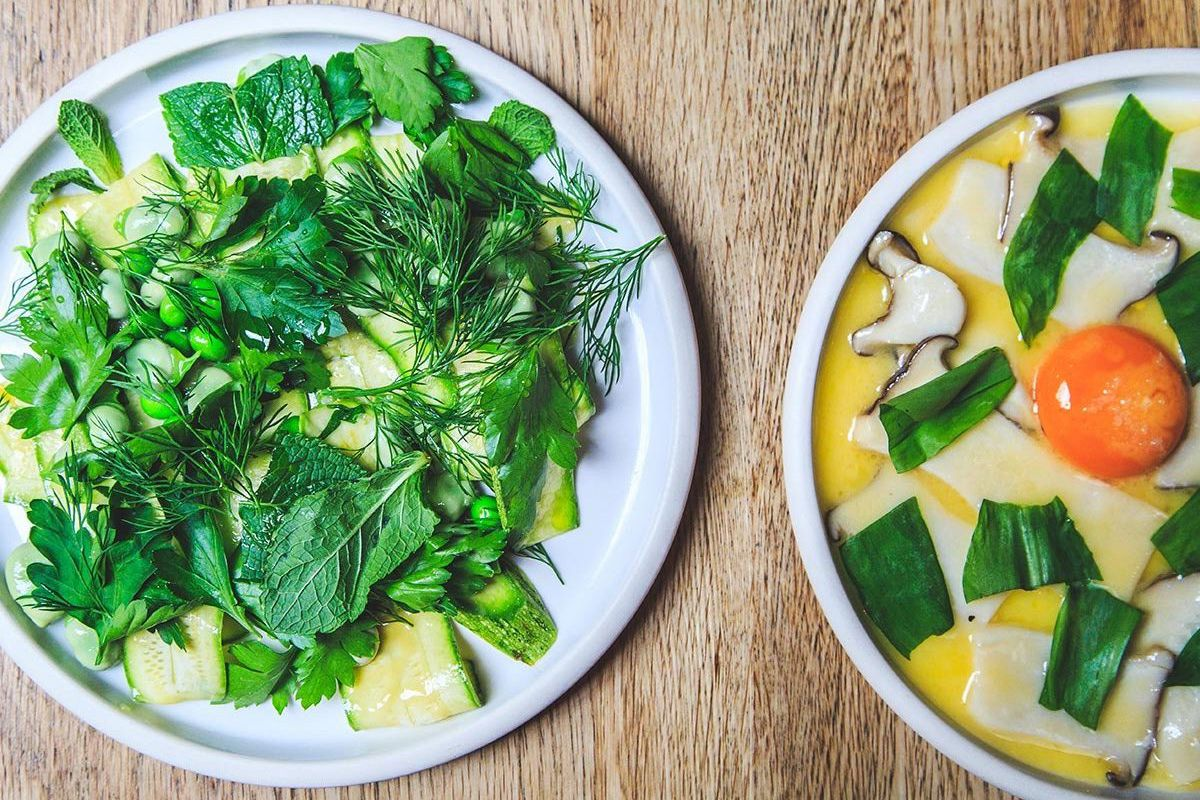 Two dishes from Elliot's Borough Market — a green salad to the left and mushrooms with egg yolk to the right — with the restaurant now opening in Hackney
