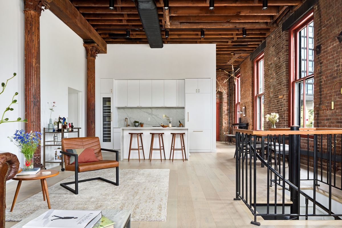 A living area with hardwood floors, a beige rug, high ceilings, and exposed brick.