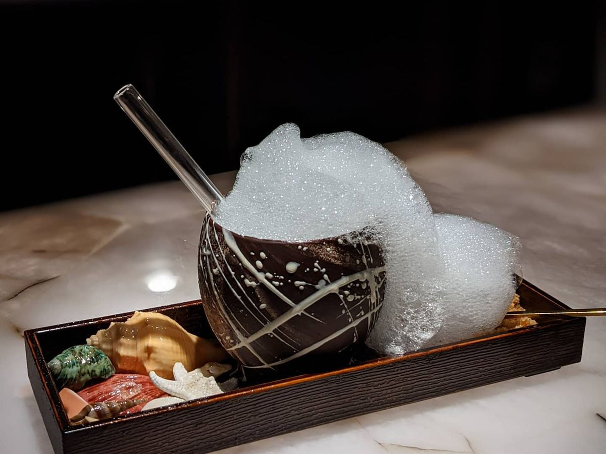 a cocktail served in a chocolate mug and garnished with seashells
