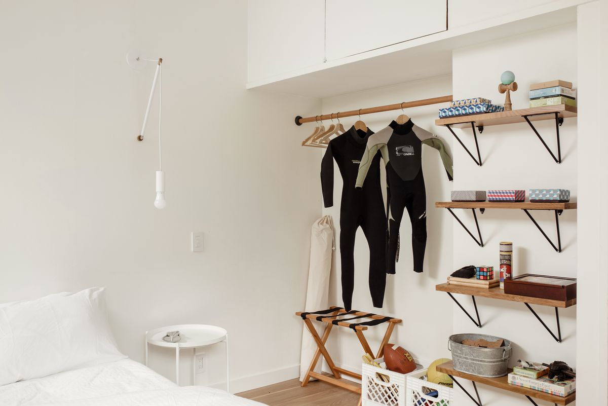 A bedroom. There is a bed with white bed linens. The walls are painted white and there are wooden shelves on the wall which are full of various objects. There is a rod with hangers and two scuba suits. A white light fixture hangs above the bed.