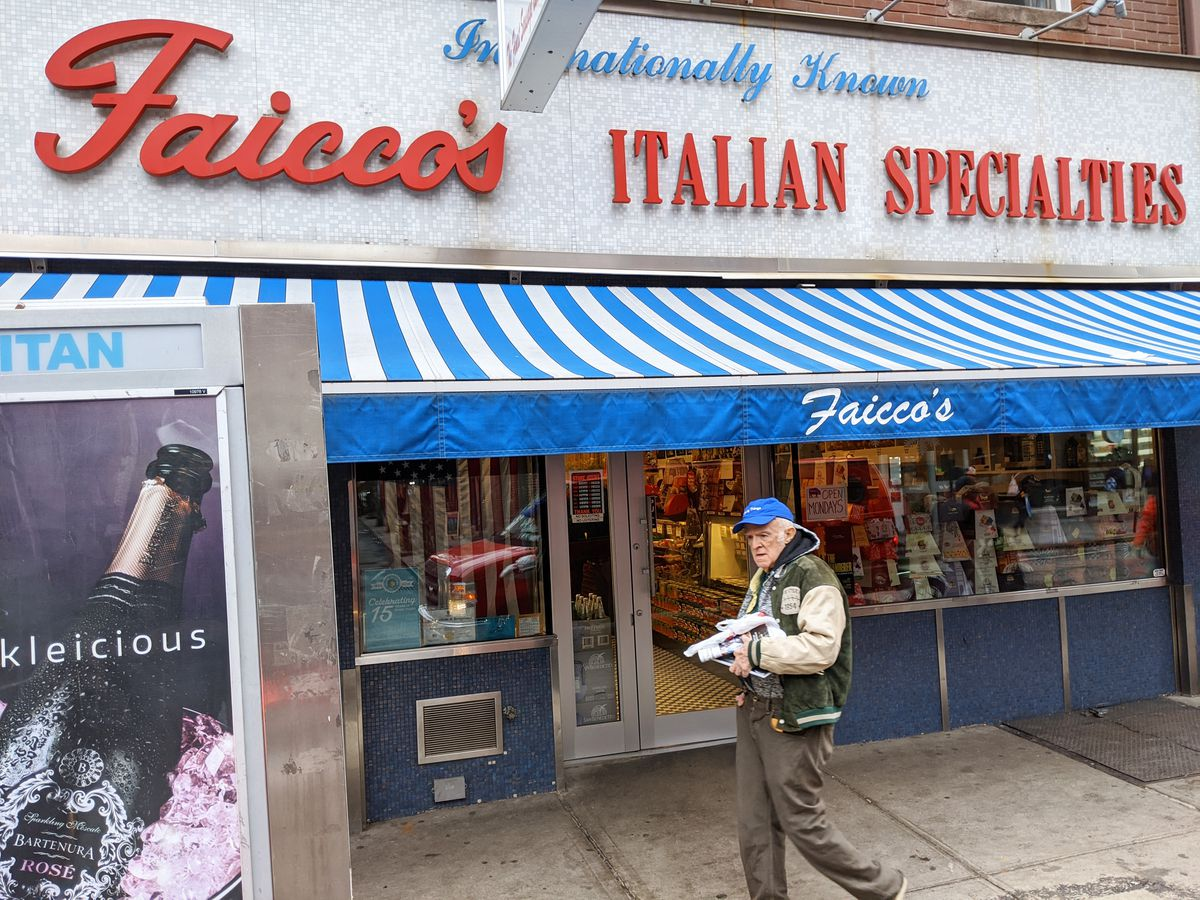 A facade with Faicco's written in red cursive, with a senior citizen standing in front and looking at the camera.
