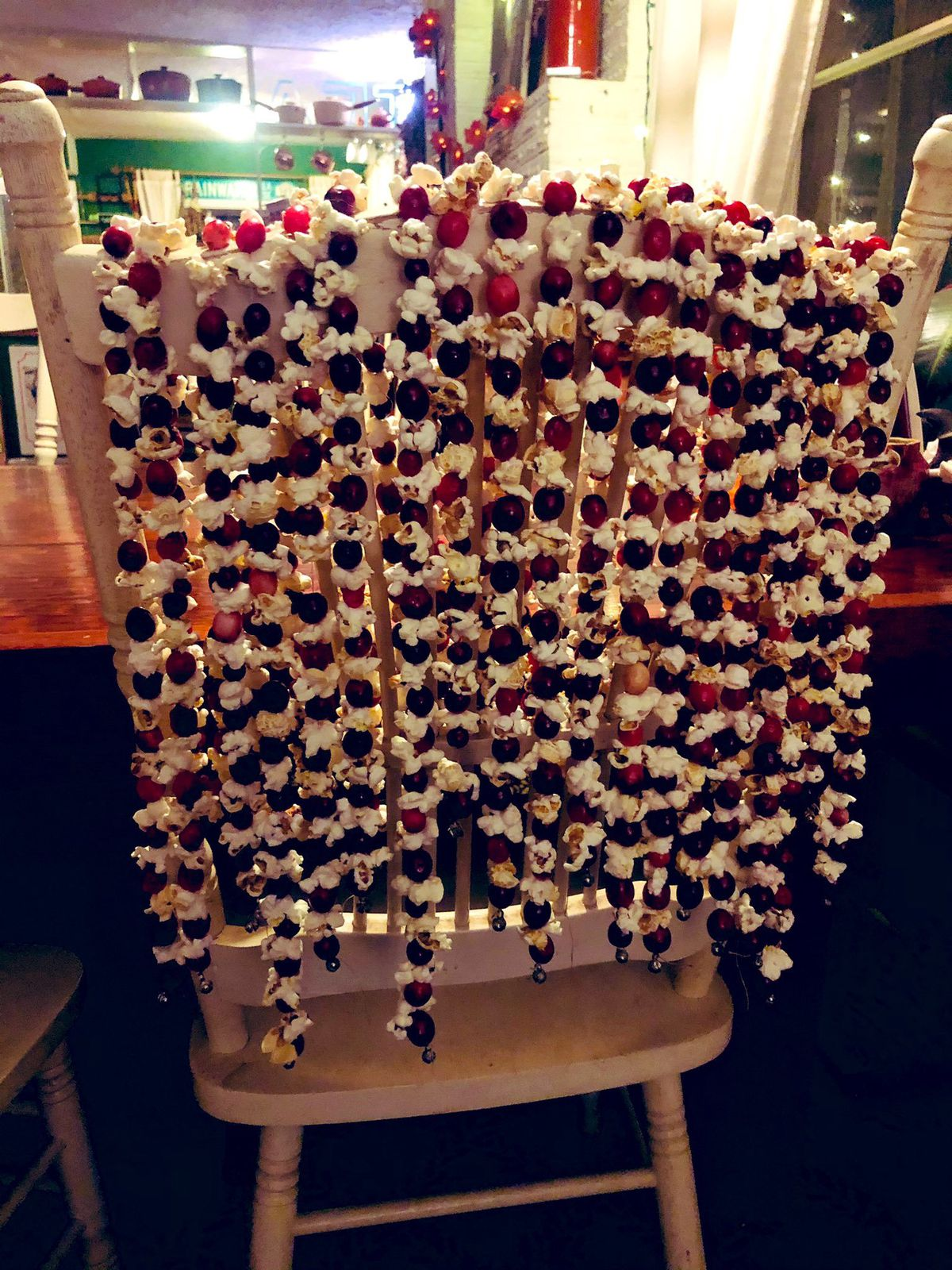 Garlands made of popcorn and cranberries, laid over a chair back.