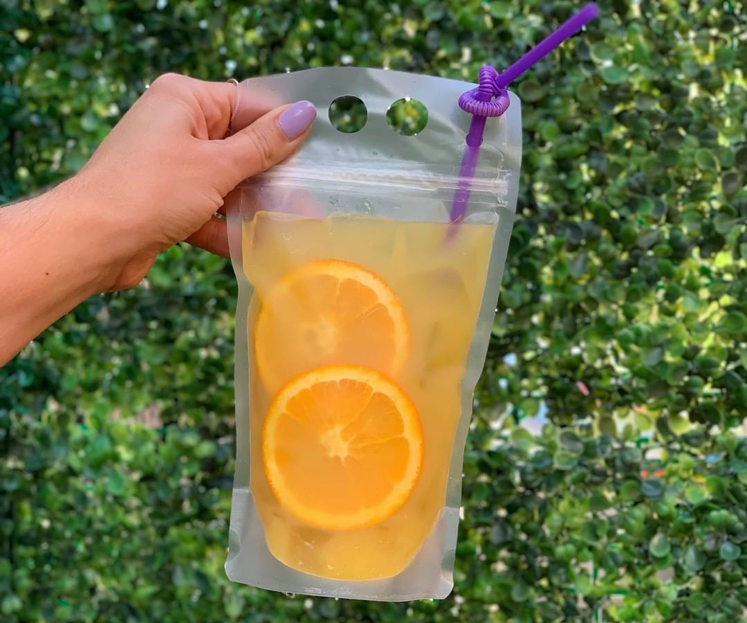 A hand holds a plastic pouch full of an orange cocktail and orange slices in front of a leafy green background