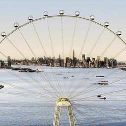 """In this image released by the New York Mayor's Office, Thursday, Sept. 27, 2012 is an artist's rendering of a proposed 625-foot Ferris wheel, billed as the world's largest, planned as part of a retail and hotel complex along the Staten Island waterfront in New York. The attraction, called the New York Wheel, will cost $230 million. Officials say the observation wheel will be higher than the Singapore Flyer, the London Eye, and a """"High Roller"""" wheel planned in Las Vegas. Beyond the wheel is the Manhattan skyline."""