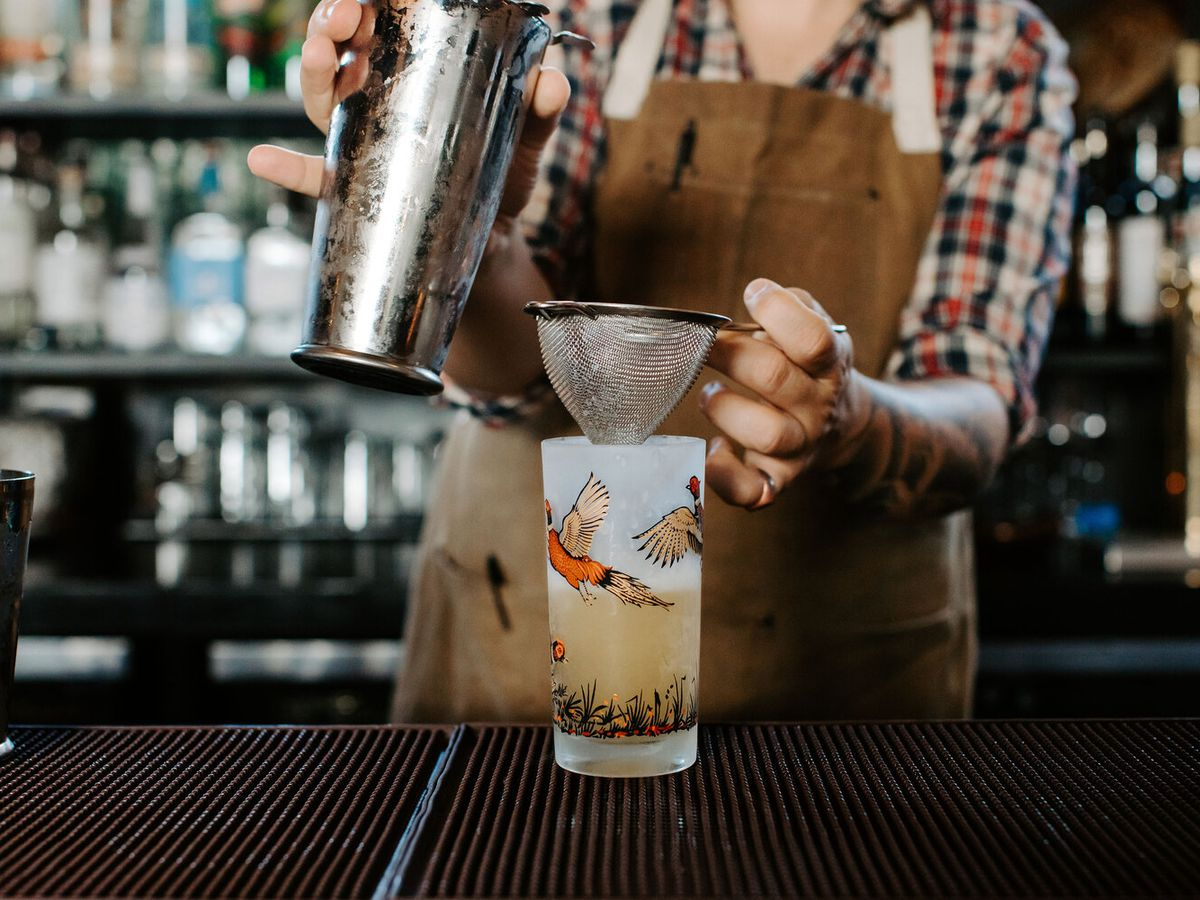 A bartender strains a cocktail into a highball glass decorated with illustrations of birds in flight on a bar with a blurred background of bottles and glasses