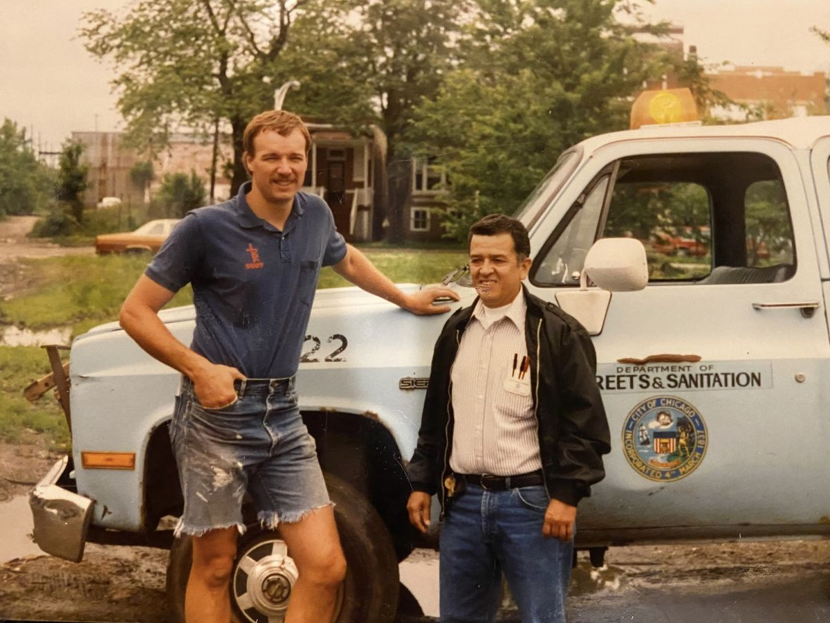 Raúl Montes, right, stands in front of his Department of Streets and Sanitation truck.