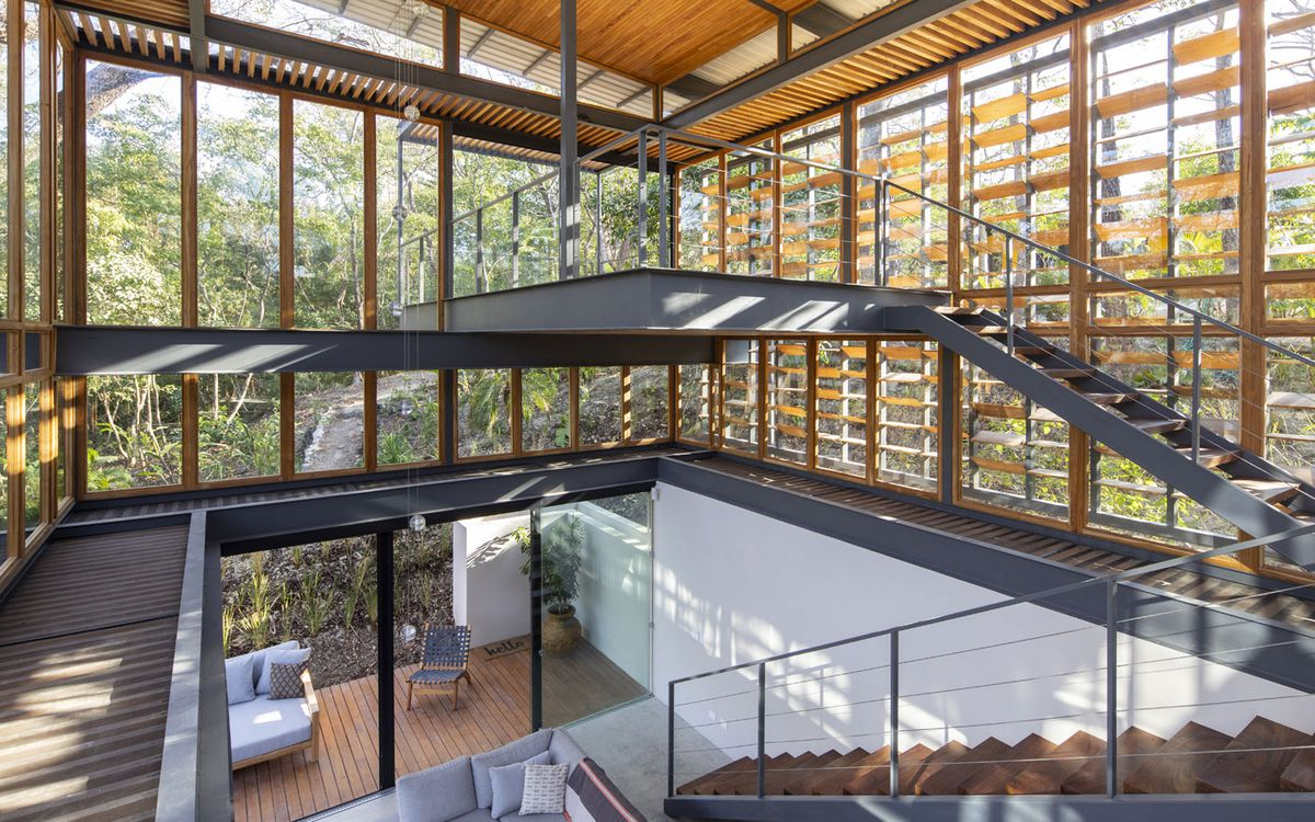 A stair case in an open air atrium area. The walls are glass. Outside, there is jungle.