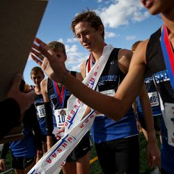 First-place finisher Carson Belnap and his teammates from Stansbury High collect their team first-place trophy in the 4A Boys State Cross-Country Championships at Highland High School in Salt Lake City on Wednesday, Oct. 23, 2019.