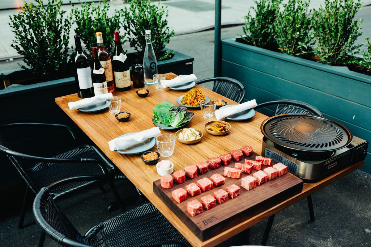 A fully-set table features the KBBQ restaurant's iconic sampling of beautifully-marbled and butchered meat for outdoor cooking on a tabletop butane grill.