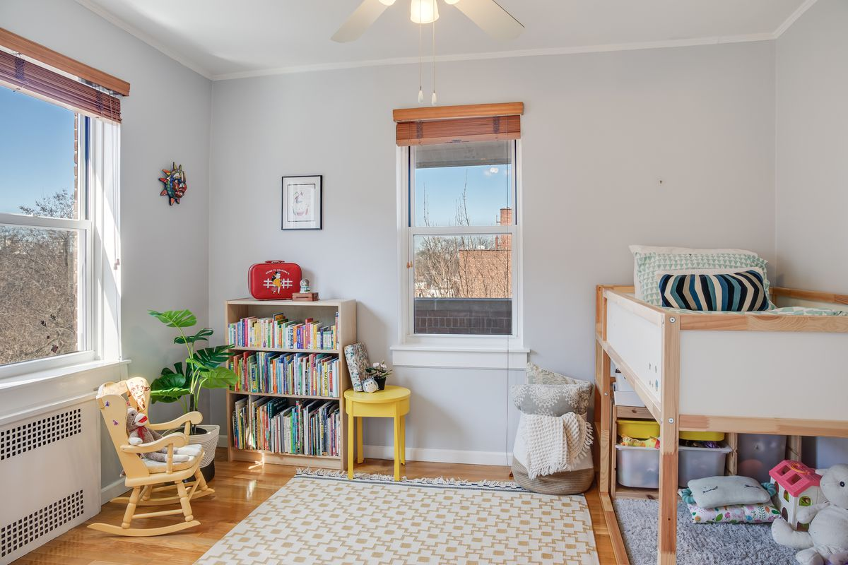 A kid's room with light grey walls, two windows, a small bookshelf, a bed, and a small rocking chair.