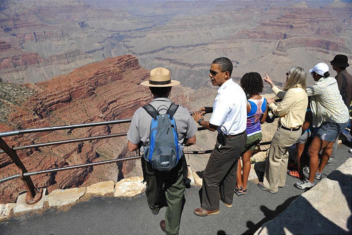 President Barack Obama, daughter Malia, wife Michelle - in white hat - and daughter Sasha - slightly hidden - talk with park ranger Scott Kraynak at the Grand Canyon on Sunday.