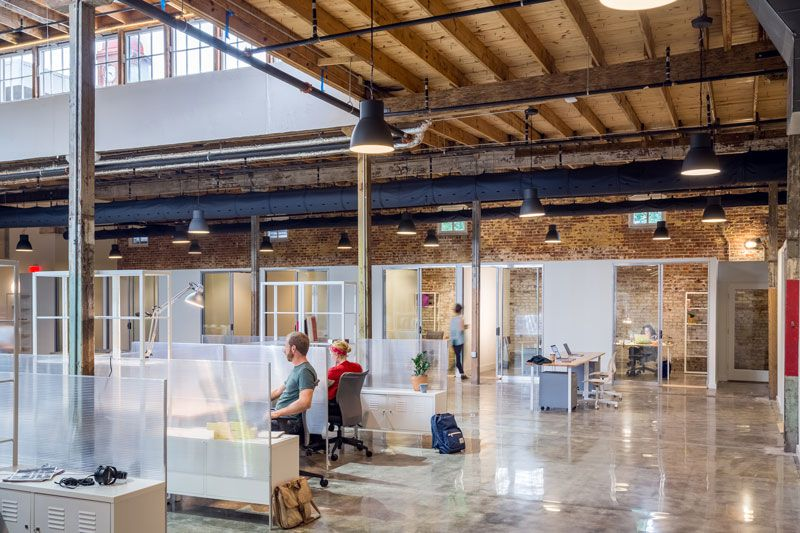 The interior of a co-working space in New Orleans. There are desks in frosted glass cubicles and a wooden ceiling. There are offices and the walls are exposed red brick.