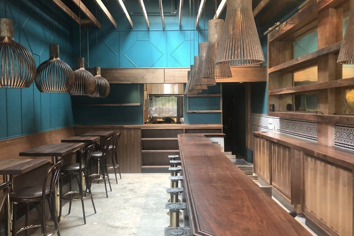 An interior of Rupee Bar in the works, with dark wood and blue walls.