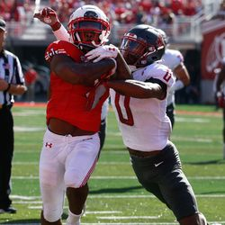 Utah running back TJ Pledger, left, gets tackled by Washington State defensive back Jaylen Watson during a touchdown of an NCAA college football game at Rice-Eccles Stadium on Saturday, Sept. 25, 2021 in Salt Lake City. Utah won the game 24-13.