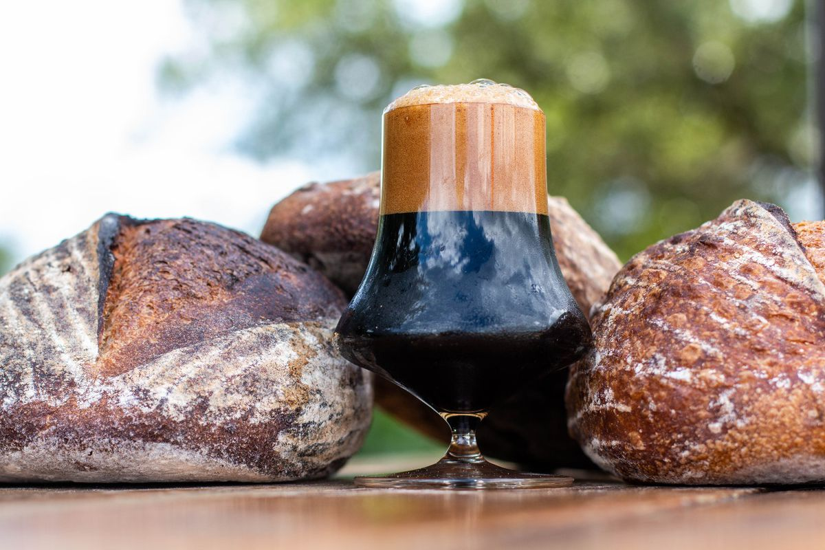 A wide beer glass with a wider center full of a dark-brown beer with a tall brown foam cap surrounded by brown loaves of bread on top of a brown table in front of trees