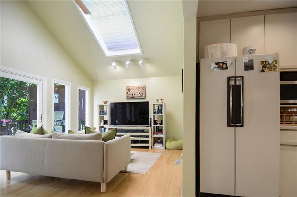 A photo of a fridge and yellow walls in a living room.