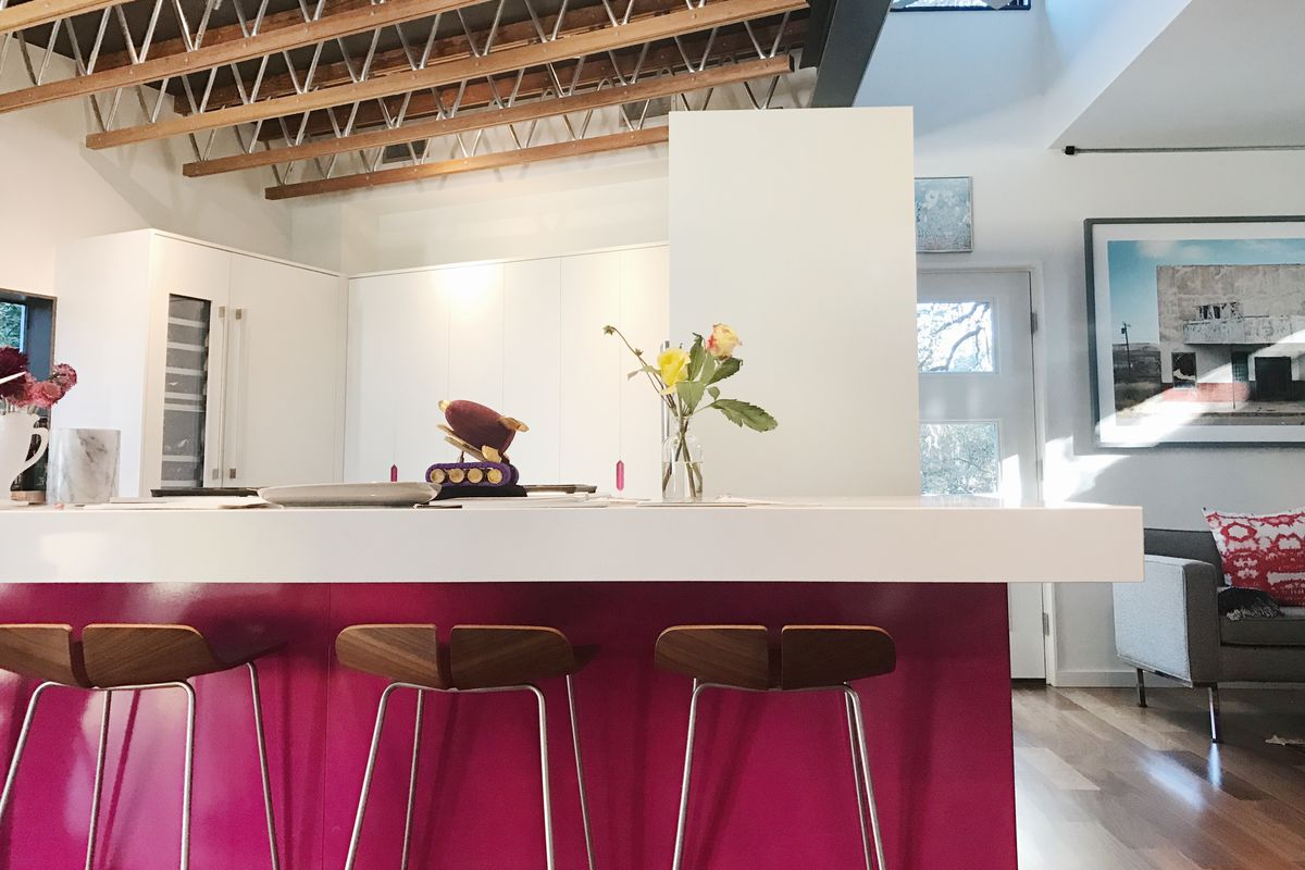 Big white open kitchen with island that's hot pink on bottom with white countertops