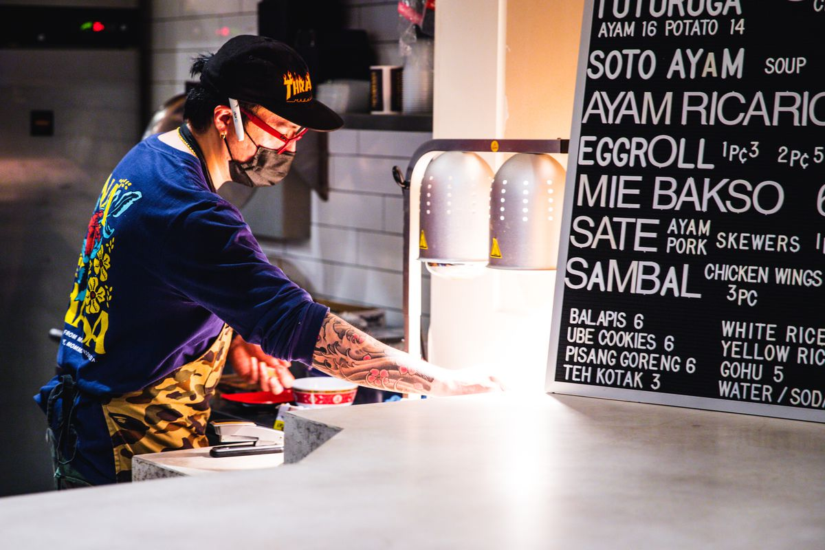 A male chef wearing a mask leans over while working in a food hall kitchen.