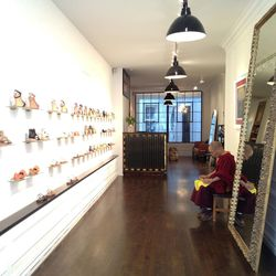 A Tibetan monk blesses the store before its Monday morning opening.