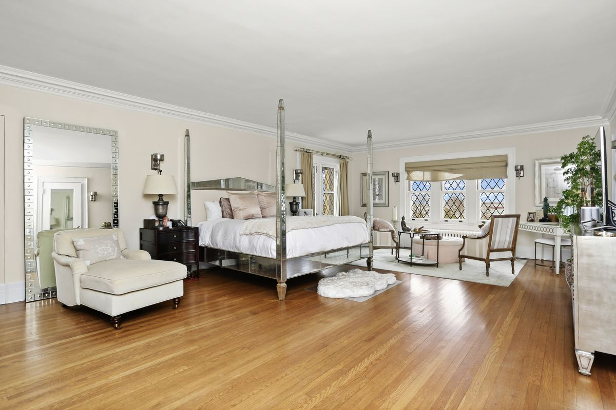 A white bedroom has wood floors, white furniture, and a four-poster bed.