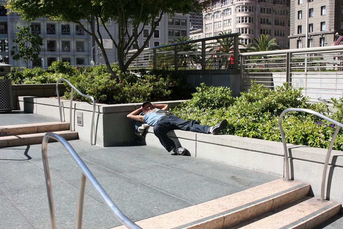 A homeless man sleeping on a cement bench in SF.