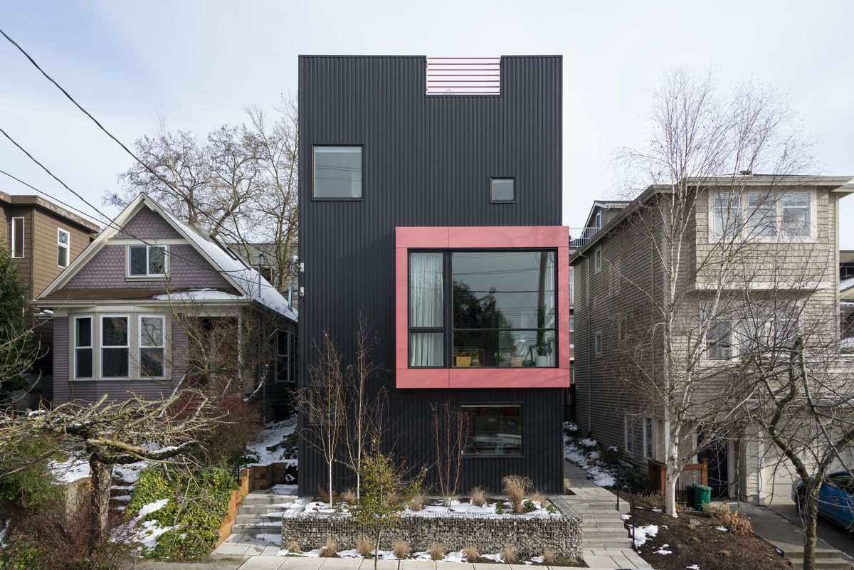 A black house with pink-framed window.