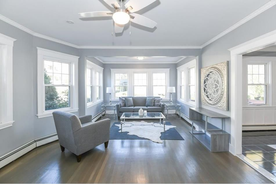 An open living groom with furniture and lots of windows, and there's a ceiling fan up top.