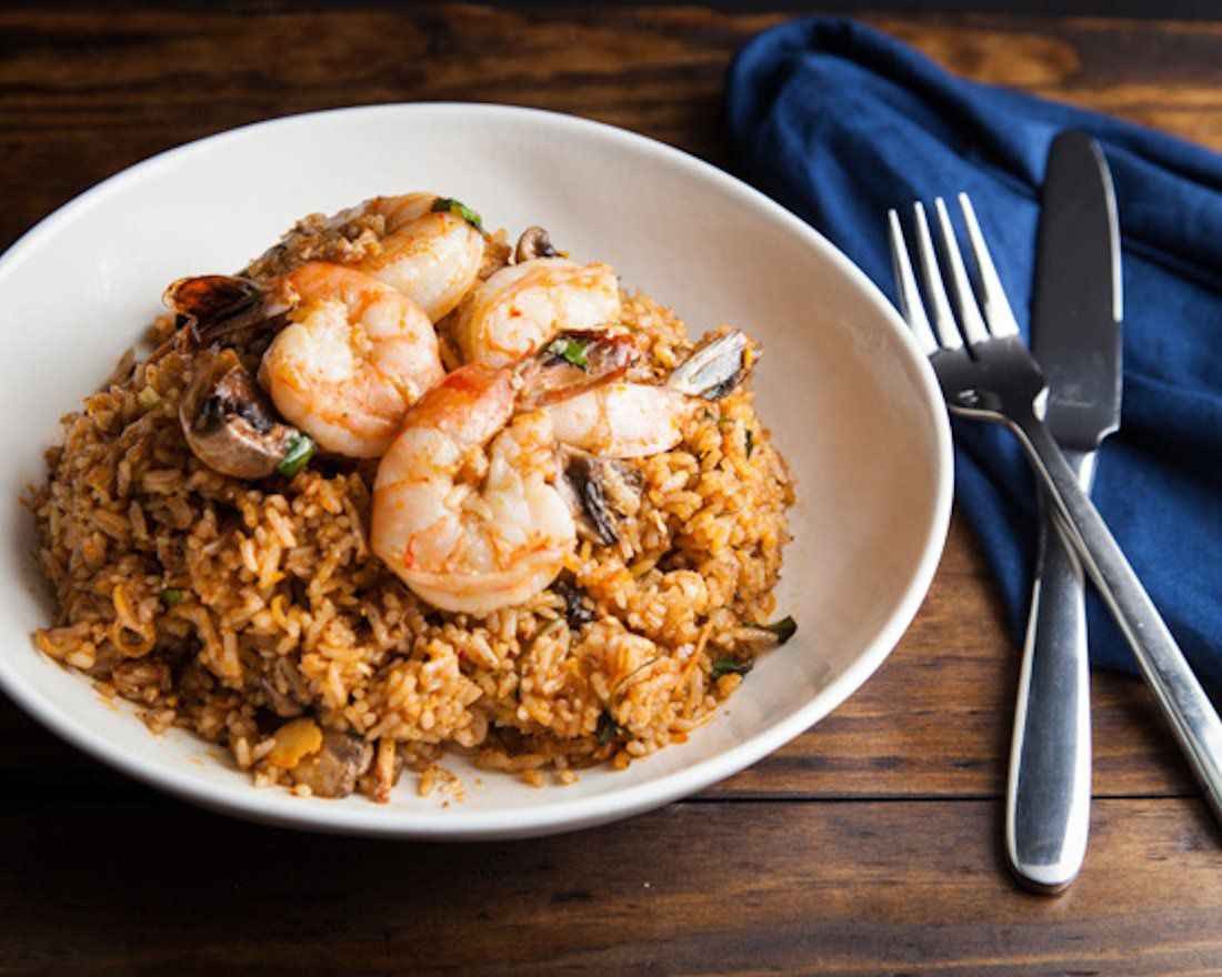 A view of a fried rice plate, topped with shrimp.