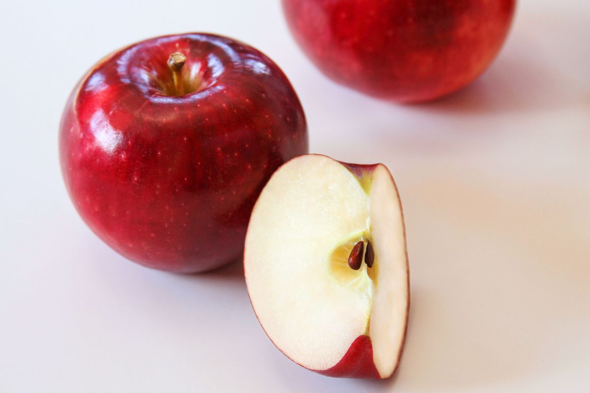 An apple, with one slice beside it.