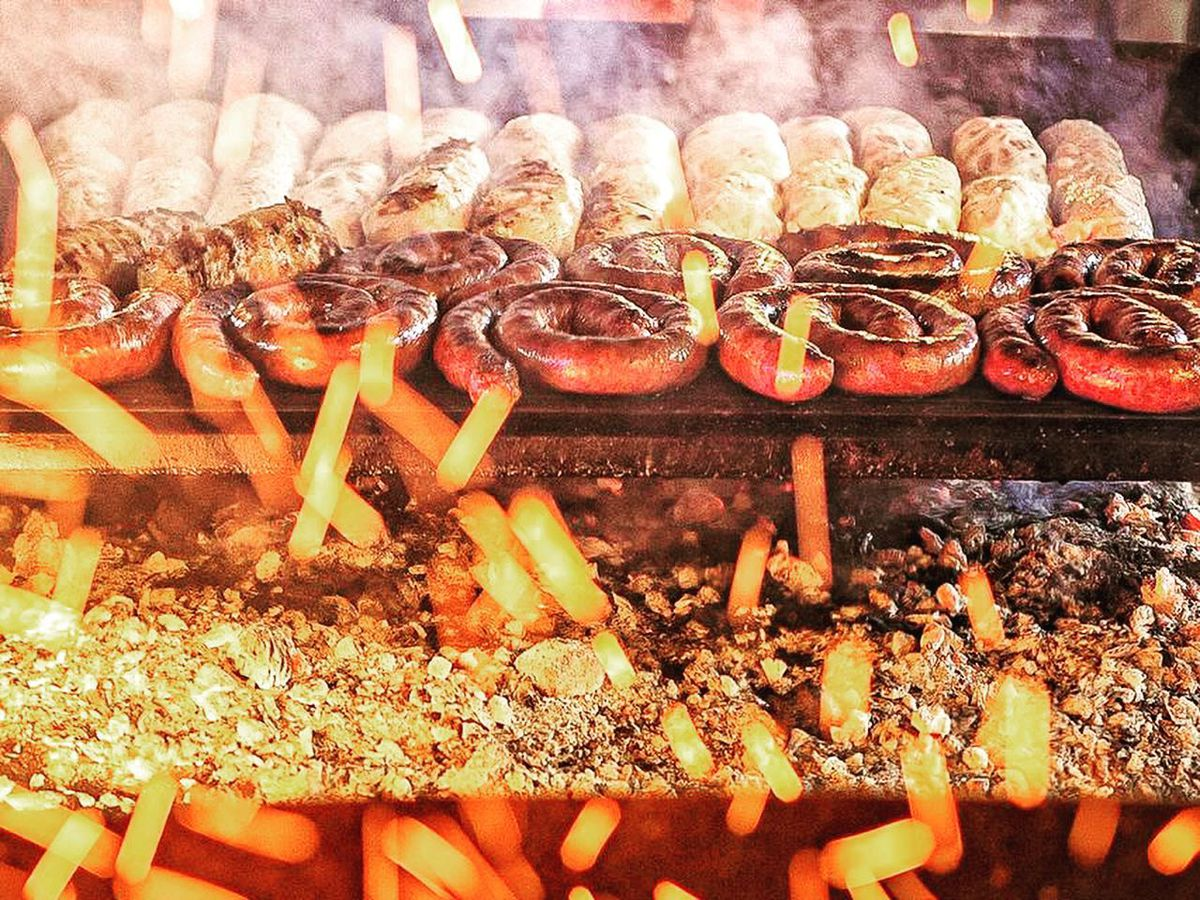 Sausages and other meats cooking on a grill beyond sparks flying in the foreground