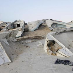 In this photo taken Sunday, Sept. 23, 2012, a Somali government soldier walks next to some of the overturned pirate skiffs that litter the dunes on the shoreline near the once-bustling pirate den of Hobyo, Somalia. The empty whisky bottles and overturned, sand-filled skiffs that litter this shoreline are signs that the heyday of Somali piracy may be over - most of the prostitutes are gone, the luxury cars repossessed, and pirates talk more about catching lobsters than seizing cargo ships.