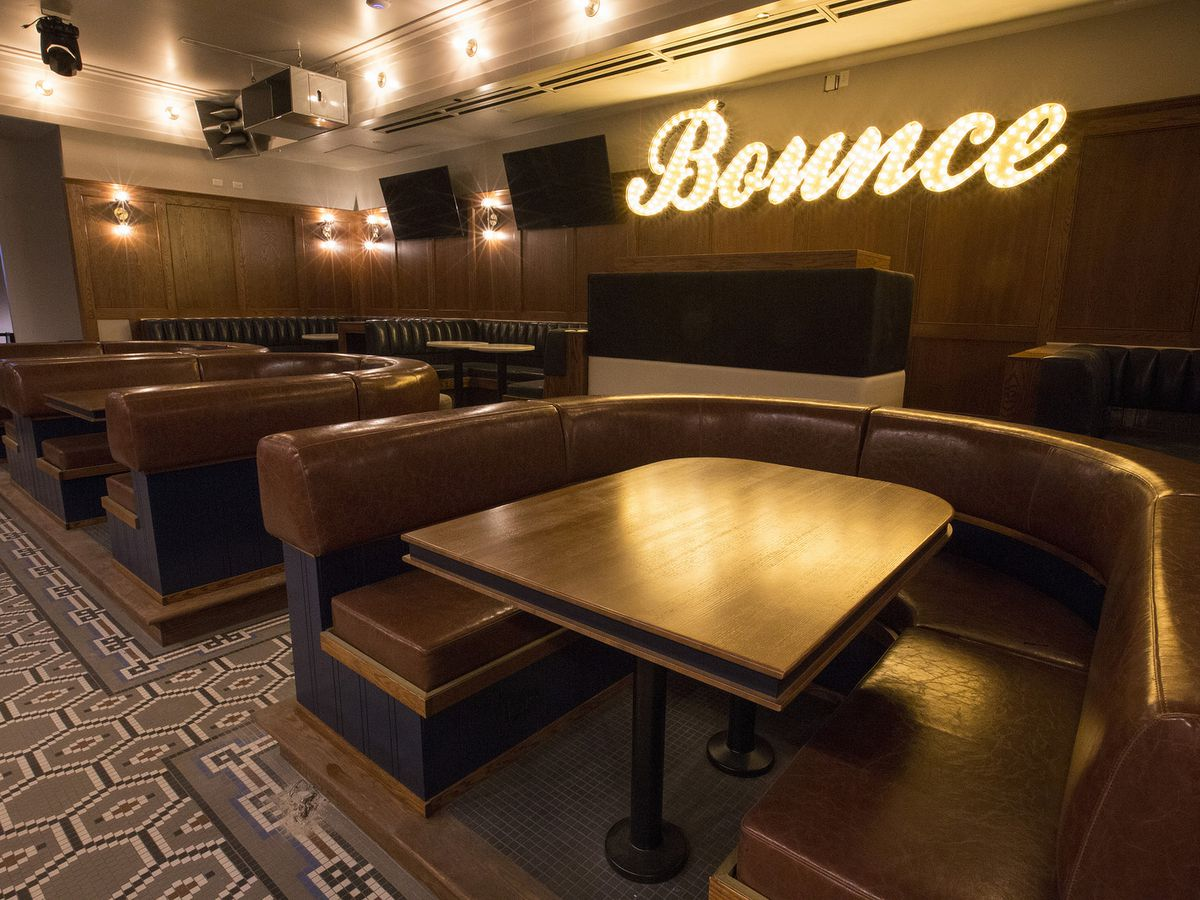 """Large U-shaped brown leather booths sit side-by-side in a low-lit room with a geometric tiled floor. A light-up sign on the wall behind the booths reads """"Bounce"""" in cursive letters."""