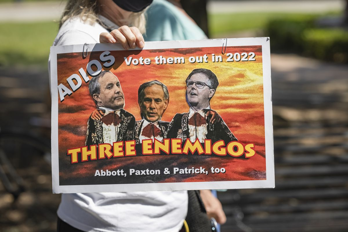 """A protest sign reads """"Adios. Vote them out in 2022. Three enemigos, Abbot, Paxton and Patrick, too."""""""