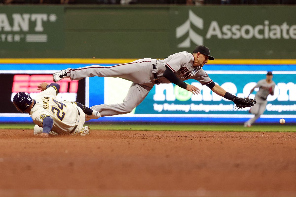 Avisail Garcia #24 of the Milwaukee Brewers slides safely into second base after Nick Ahmed #13 of the Arizona Diamondbacks is unable to field a throw during the fifth inning at American Family Field