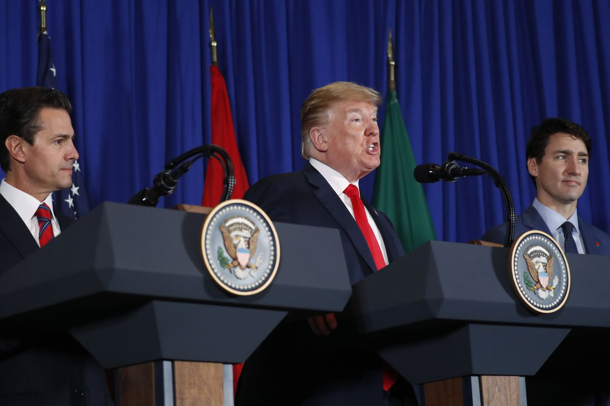 President Donald Trump speaks during the USMCA signing ceremony as Canada's Prime Minister Justin Trudeau, right, and Mexico's President Enrique Pena Neto, left, look on, Friday, Nov. 30, 2018, in Buenos Aires, Argentina.