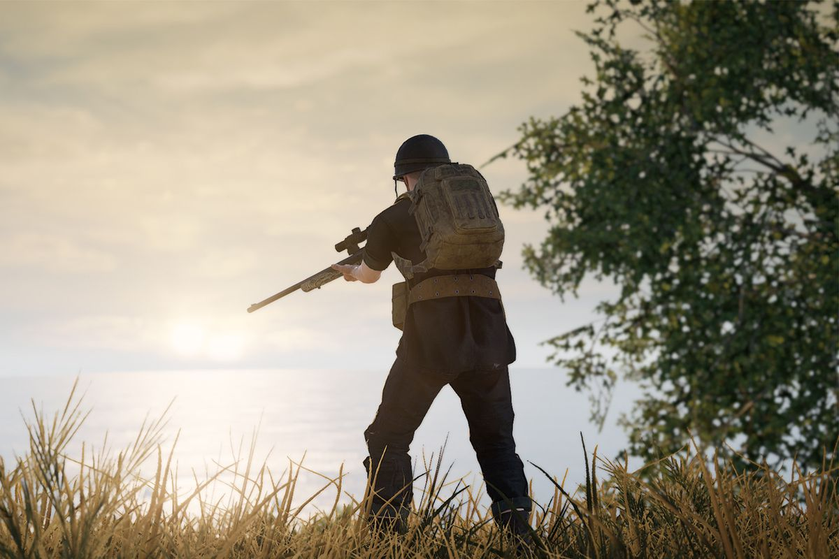 A PUBG player stands on a hilltop aiming a scoped rifle downward with the sun in the background