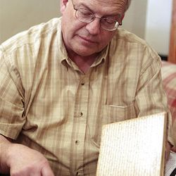 Brent F. Ashworth looks over the McLellin journal.