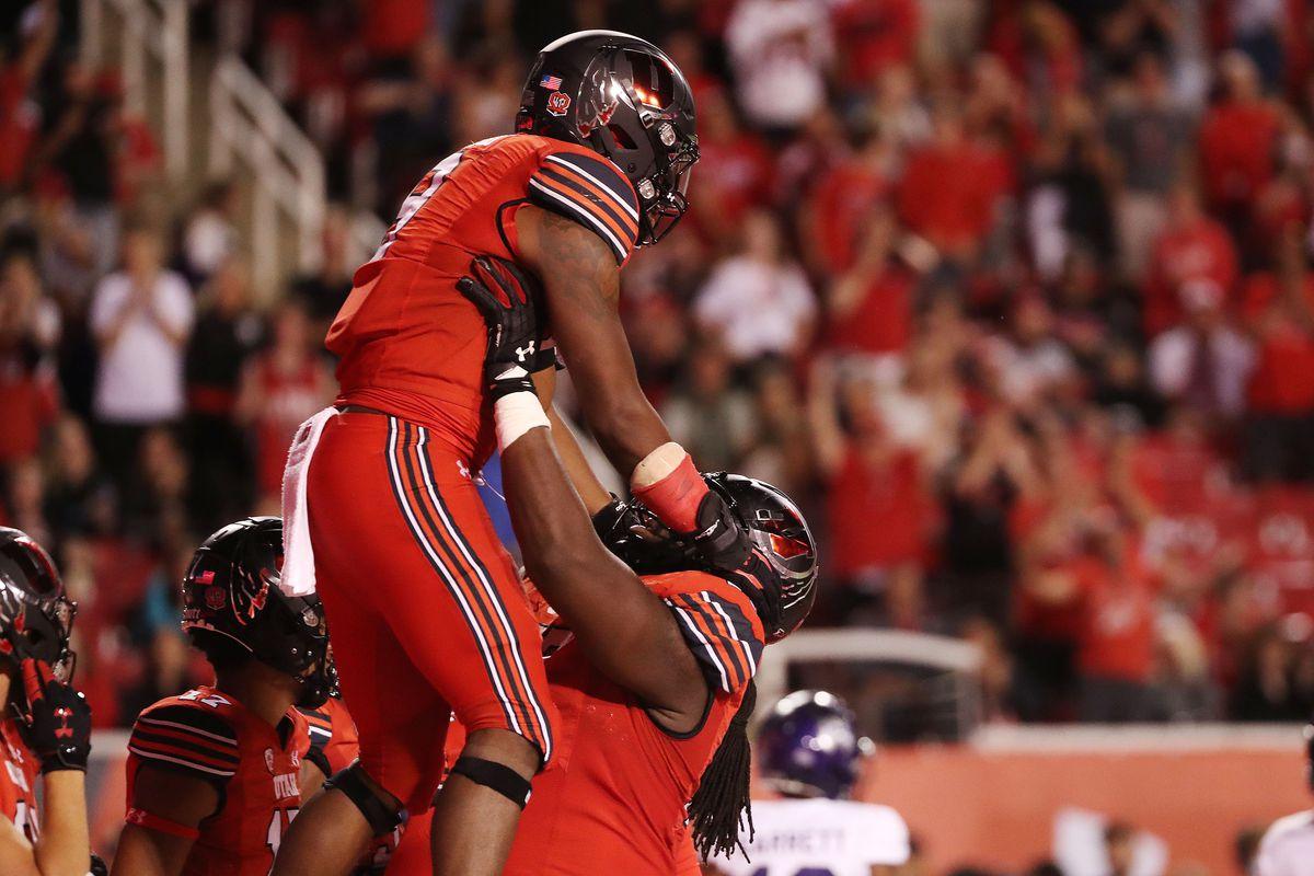 Utah running back Tavion Thomas celebrates his touchdown with offensive lineman Bamidele Olaseni in Salt Lake City.