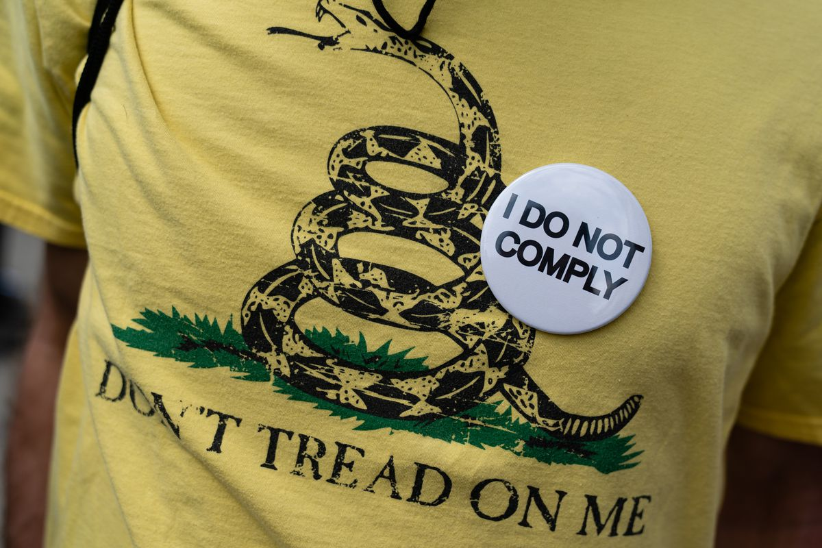 """A person wears an """"I Do Not Comply"""" pin on a """"Don't tread on me"""" t-shirt at a protest against masks, vaccines, and vaccine passports."""