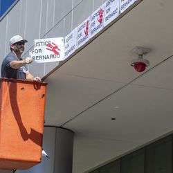 A worker removes the last of hundreds of signs that were plastered by protesters on the Salt Lake County District Attorney's Officebuilding in Salt Lake City on Friday, July 10, 2020. The building suffered tens of thousands of dollars in damage when protesters broke out at least three windows and spread red paint over large portions of the building and area in front of the structure on Thursday.