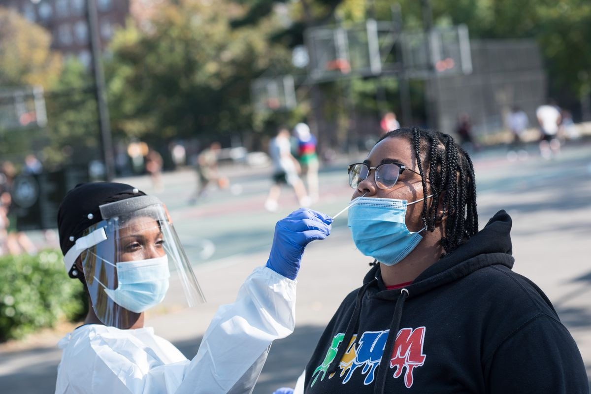 A woman with a face shield and masks swabs the nose of another masked woman outdoors
