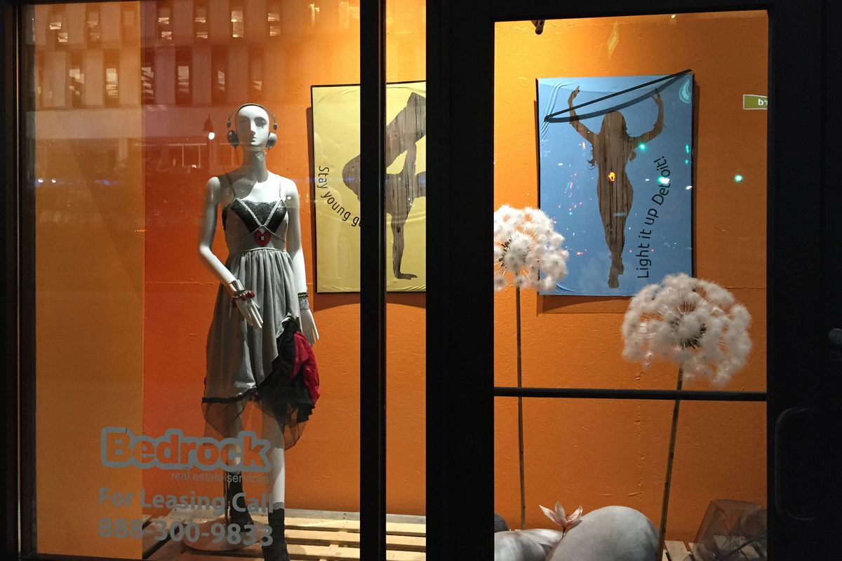 While Gilbert's real estate arm waits for first-floor retailers to move in, fanciful window displays for imaginary stores fill the space.