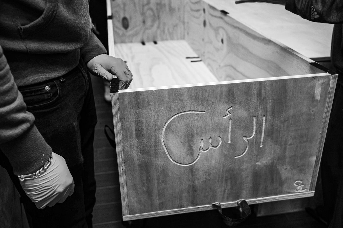 Inscribed on a wooden casket is an Arabic word indicating where the deceased's head is. Muslims are buried with their head facing toward the Kaaba, the structure at the heart of the Great Mosque in Makkah, Islam's holiest site.