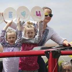 Young girls hold a sign as the Highland City Youth Council, city officials, police officers and firefighters participate in a drive-by parade for the residents of Highland Glen Assisted Living in Highland on Wednesday, May 13, 2020 to show love and support for them.