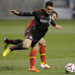 Real Salt Lake midfielder Kyle Beckerman (5) upends Toronto FC forward Gilberto Oliveira Souza Junior (9) during a game at Rio Tinto Stadium in Sandy on Saturday, March 29, 2014.