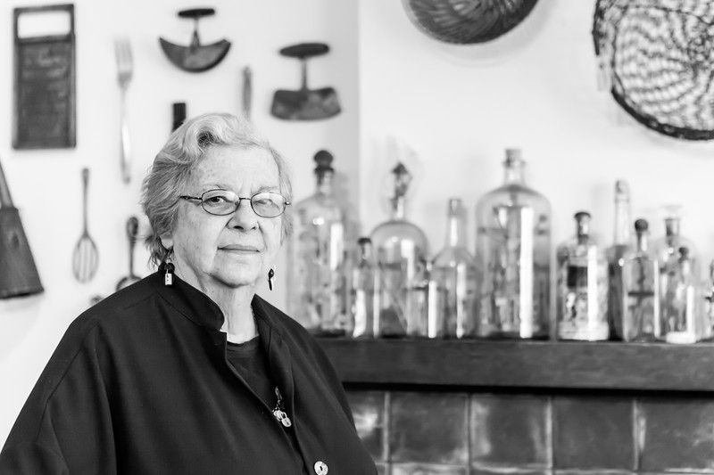 A woman stands in front of a shelf with glass jars that hold various objects.