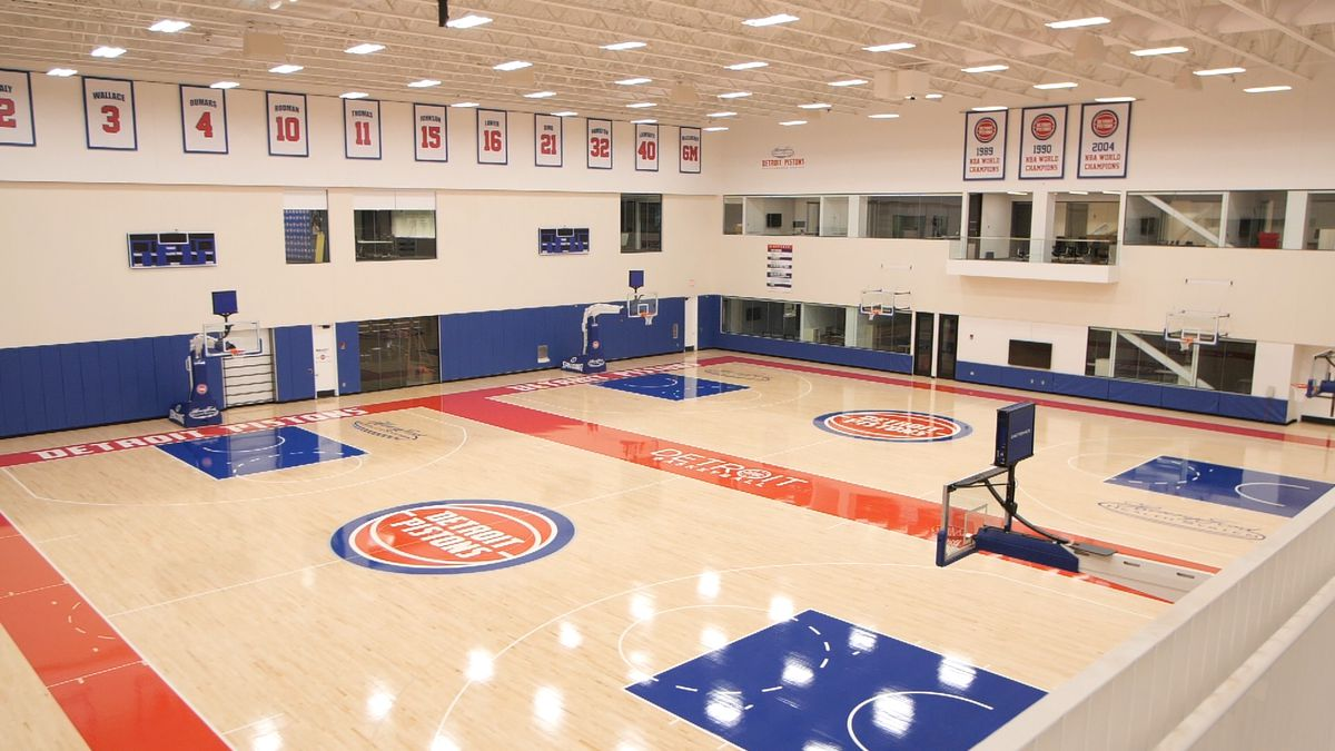 Two basketball courts with red and blue paint and Detroit Pistons logo in the center.