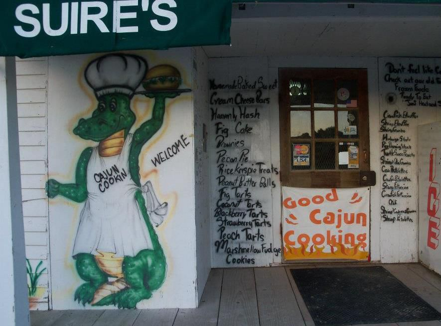 The exterior wall of a restaurant and grocery, painted with an alligator and the menu